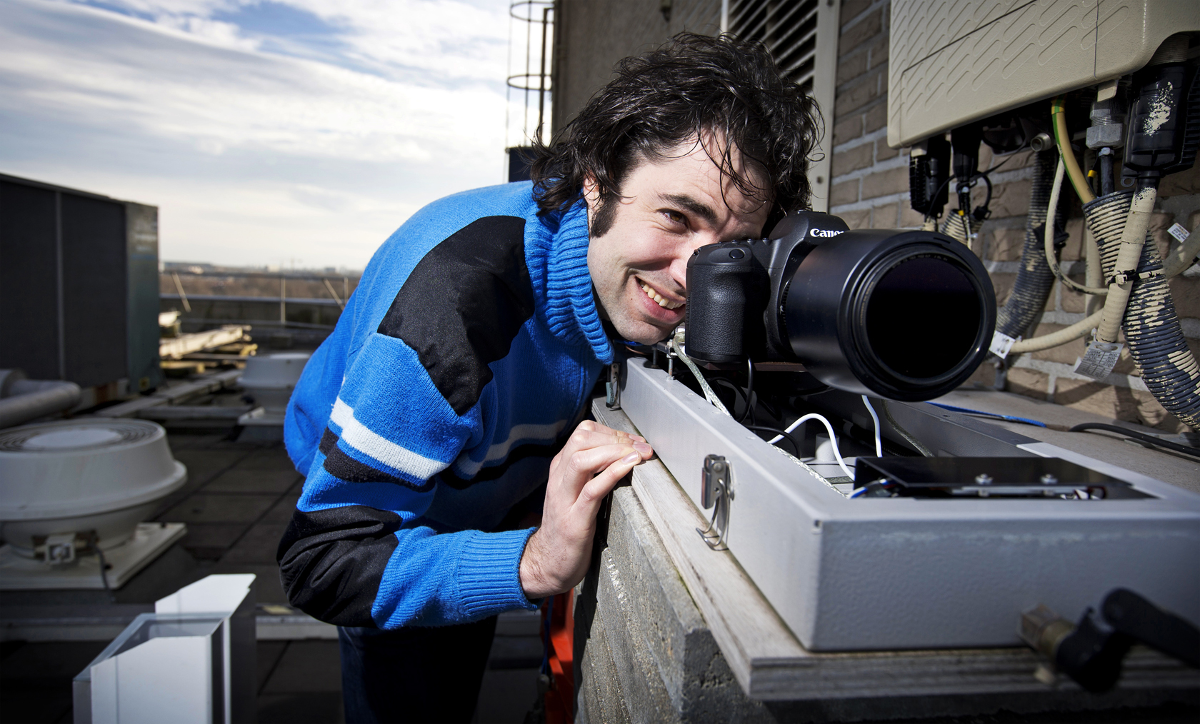 Foto: fotograaf kijkt door zijn lens